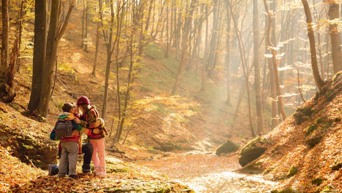 Mother embracing her children while hiking in beautiful forest at autumn
