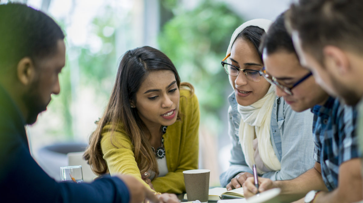 A multi-ethnic group of business people are indoors in an office boardroom. They are sitting around a table and making plans. An Ethnic woman is explaining papers to her coworkers.