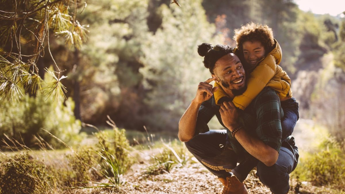 Dad and son bonding and having fun with piggyback ride on mountain hiking adventure